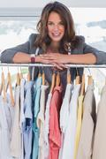 Stock Photo of Smiling fashion designer leaning on clothes