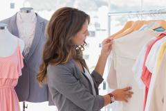 Stock Photo of Fashion designer looking at clothes
