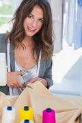 Fashion designer cutting textile next to a sewing machine Stock Photos