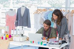 Two fashion designers working on laptop - stock photo