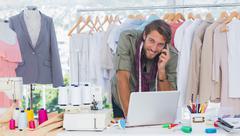 Smiling fashion designer using laptop - stock photo