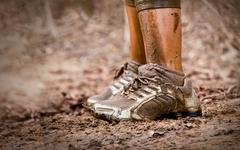 Mud race runner's shoes Stock Photos