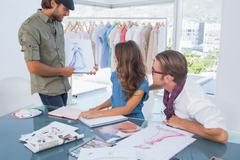 Fashion designer presenting his draw to colleagues - stock photo