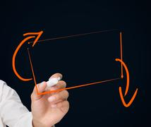 Businessman drawing orange rectangle - stock photo