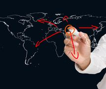 Businessman drawing world map with arrows - stock photo