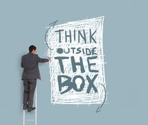 Businessman drawing think outside the box message Stock Photos