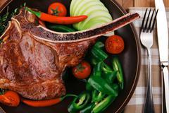 Meat food : roast rib on dark dish Stock Photos