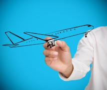 Businessman drawing black airplane - stock photo