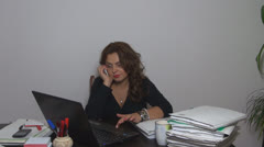 Young businesswonan working on laptop in her office.Talking on the phone Stock Footage