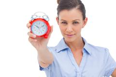Businesswoman showing alarm clock - stock photo