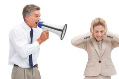Mature businessman shouting at his coworker with megaphone - stock photo