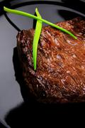 Stock Photo of meat food : roasted fillet mignon on black plate with chives
