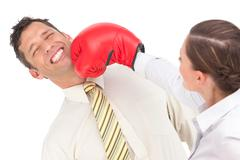 Businesswoman punching businessman with boxing gloves - stock photo