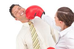 Businesswoman knocking out a businessman with boxing gloves - stock photo