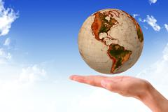 globe in human hand against blue sky. environmental protection concept - stock photo