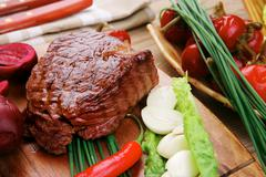beef grilled and garnished with green lettuce and red hot pepper - stock photo