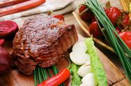 Stock Photo of beef grilled and garnished with green lettuce and red hot pepper