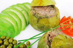 Round zucchini filled mince meat served with tomatoes and peas Stock Photos