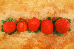raw ripe strawberry on wood - stock photo