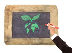 drawing of the earth surrounded   on a chalkboard - stock photo