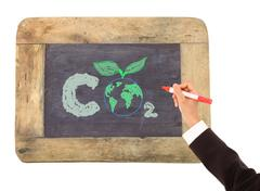 drawing of the earth surrounded   on a chalkboard - stock illustration