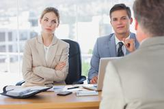 Happy business people interviewing business man Stock Photos