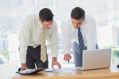 Businessmen working together leaning on desk Stock Photos