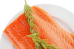 big salmon fillet on white with rosemary - stock photo