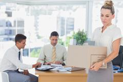 Businesswoman leaving office after being fired - stock photo