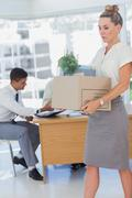 Businesswoman holding a box and his colleagues in the bottom - stock photo
