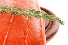 salmon fillet on wood plate and rosemary - stock photo