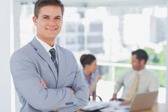 Smiling businessman and his colleagues in background - stock photo