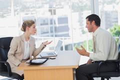 Businesswoman interviewing a smiling businessman Stock Photos