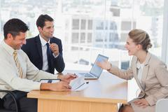 Business people laughing with interviewee - stock photo