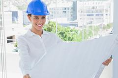 Stock Photo of Cheerful architect rolling out a blueprint