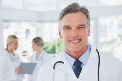 Smiling grey haired doctor standing in his office - stock photo