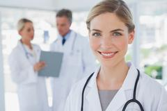 Smiling blonde haired doctor standing in her office - stock photo