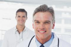 Stock Photo of Smiling doctor standing in front of his colleague