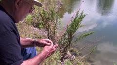 Elderly man baiting hook while fishing Stock Footage