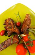 Served entree: ribs on plate with hot peppers Stock Photos