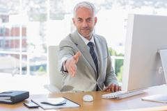 Stock Photo of Smiling businessman reaching out hand for handshake