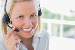 Stock Photo of Businesswoman with headset smiling at camera