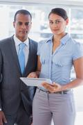 Stock Photo of Business team with tablet pc smiling at camera