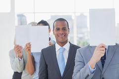 Businessman smiling at camera with colleagues covering faces - stock photo