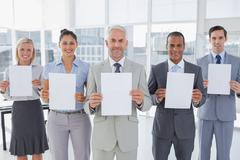 Stock Photo of Buisness team holding up blank pages