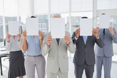 Stock Photo of Buisness team holding up blank pages and covering their faces