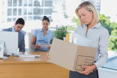 Sad businesswoman leaving office after being let go - stock photo