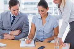 Businesswoman showing colleagues something on notepad Stock Photos