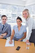 Business people at desk with notepad smiling at camera Stock Photos