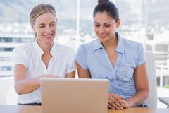 Businesswomen looking at laptop - stock photo